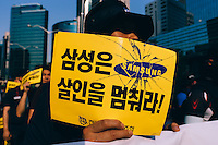 SEOUL, Korea, May 30 - A worker holding up a sign &quot;Samsung, stop killing!&quot; marches in protest through pavements of Gangnam in front of SamsungHQ.<br /> <br /> The sign refers to a recent suicide of a union worker, as well as leukemia and other illness victims from Samsung semi-conductor plants.