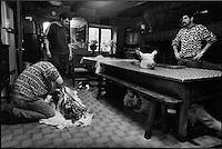 Europe/France/Auvergne/15/Cantal/Massif du Puy Mary/ Mandailles ; Jour de la Fète du Cochon ou Tuade chez Daniel Reygade -Parc Naturel Régional des Volcans d'Auvergne- le chat passe les enfants cachés sous la table regardent