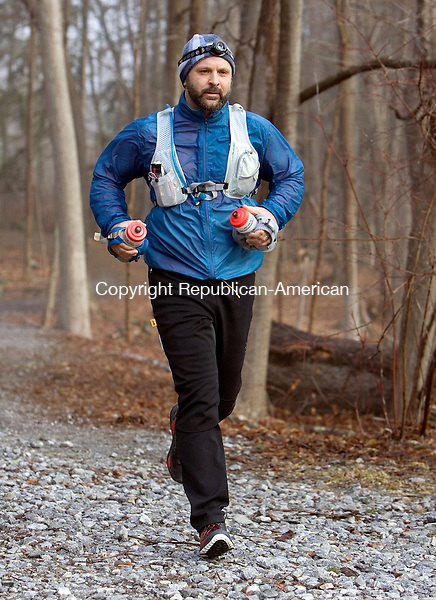 MIDDLEBURY CT. 06 March 2015-040615SV01-Scott White of Middlebury runs on a trail at Hop Brook in Middlebury Monday. White will run 100 miles in late April to raise money for NEADS, a nonprofit that provides service dogs to combat veterans. <br /> Steven Valenti Republican-American
