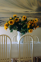 An antique enamel jug filled with sunflowers stands on a table in front of a landscape painting by Cyril Vassiliev in the dining room