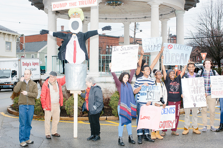 "Protesters stand outside the venue before real estate mogul and Republican presidential candidate Donald Trump speaks at a rally at Exeter Town Hall in Exeter, New Hampshire, on Thurs., Feb. 4, 2016. A large puppet with a toilet seat for a face reads ""Dump the Trump."" At right, a group of students from the Phillips Exeter Academy boarding school take part in the protest."