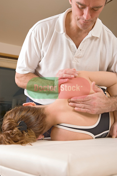 physiotherapist manipulates womans back and shoulder