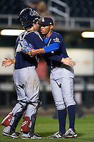 New Hampshire Fisher Cats catcher Jack Murphy (9) and pitcher Jimmy Cordero (30) embrace after the final out of a game against the Harrisburg Senators on July 21, 2015 at Metro Bank Park in Harrisburg, Pennsylvania.  New Hampshire defeated Harrisburg 7-1.  (Mike Janes/Four Seam Images)