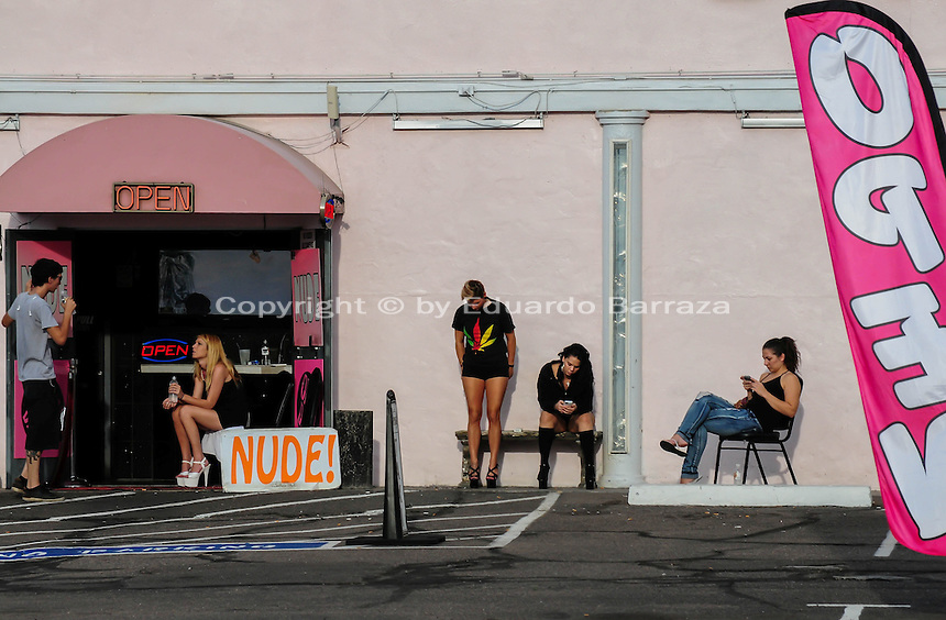 """Tempe, Arizona. Employees of an adult entertainment center take a break outside the night club on a summer afternoon. Four women and a man wait outside the business where a """"nude"""" sign is sign by the entrance."""