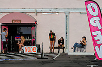 "Tempe, Arizona. Employees of an adult entertainment center take a break outside the night club on a summer afternoon. Four women and a man wait outside the business where a ""nude"" sign is sign by the entrance."