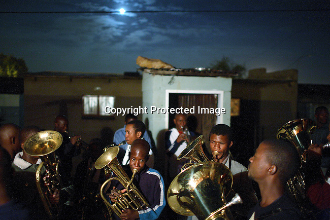 Members of a brassband rehearse after dark in a backyard on Soweto
