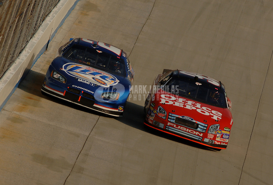 June 4, 2006; Dover, DE, USA; Nascar Nextel Cup driver Carl Edwards (99) passes Kurt Busch (2) during the Neighborhood Excellence 400 at Dover International Speedway. Mandatory Credit: Mark J. Rebilas..