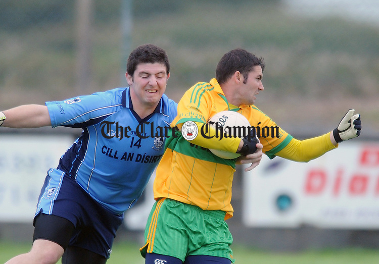 Kildysart's Keith Murphy puts in a tackle on Brian Troy. Photograph by Declan Monaghan
