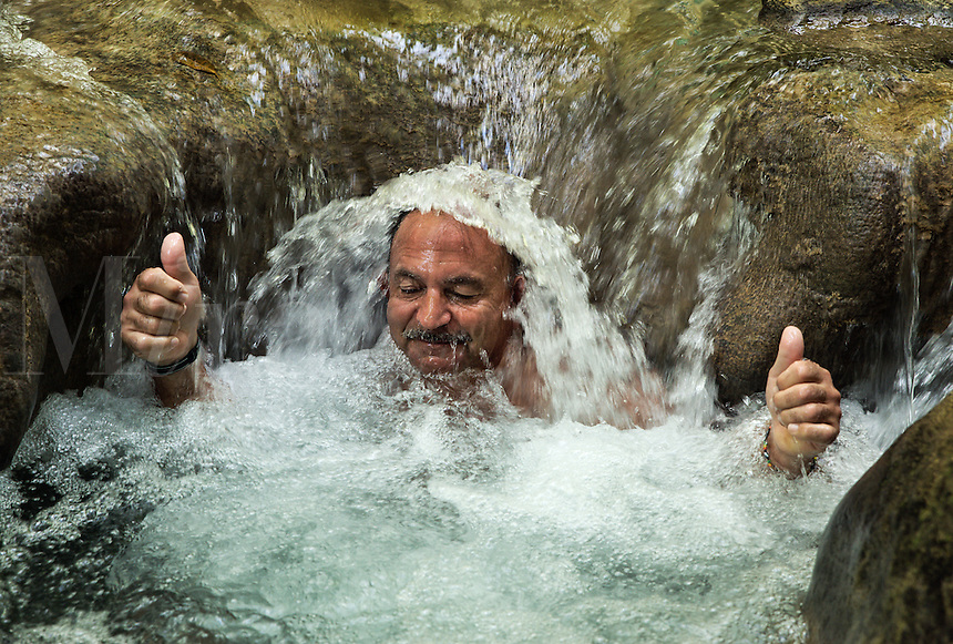 Man enjoys a refreshing water massage at Mayfield Falls, Glenbrook, Jamaica