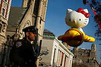 """A New York Police officer stands guard while the """"Hello Kitty"""" balloon is seen during the 89th Macy's Thanksgiving Annual Day Parade in the Manhattan borough of New York.  11/26/2015. Eduardo MunozAlvarez/VIEWpress"""