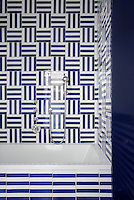 Another hotel bathroom is decorated with blue and white striped ceramic tiles laid in a graphic pattern by Vietri Scotto