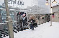 A family maneuvers on the snowy platform at the Queensboro Plaza station in New York during Winter Storm Jonas on Saturday, January 23, 2016. Due to blizzard conditions approaching the MTA announced they will be suspending all above ground subway service as of 4:00 PM. (© Richard B. Levine)