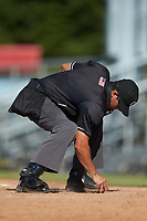 Home plate umpire Justin Juska cleans off home plate during the Appalachian League game between the Bristol Pirates and the Danville Braves at American Legion Post 325 Field on July 1, 2018 in Danville, Virginia. The Braves defeated the Pirates 3-2 in 10 innings. (Brian Westerholt/Four Seam Images)