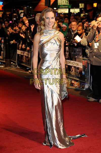"HILARY SWANK.The 54th BFI London Film Festival screening of ""Conviction"" at Vue cinema, Leicester Square, London, England, UK, October 15th 2010 .LFF full length sleeveless silver shiny metallic wavy hair dress gold long maxi clutch bag smiling  .CAP/WIZ.© Wizard/Capital Pictures."