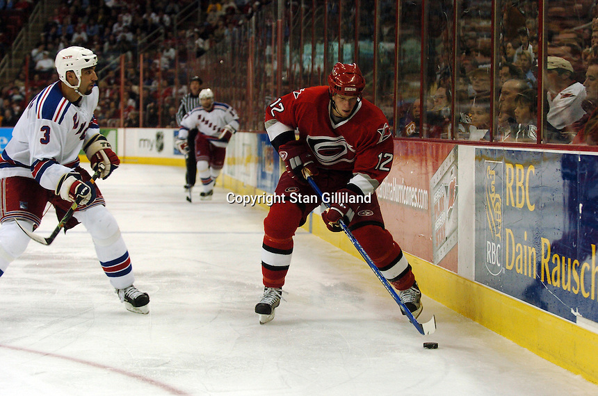 Carolina Hurricanes' Eric Staal (12) collects the puck along the boards as the New York Rangers' Michal Rozsival (3) approaches Tuesday, March 14, 2006 at the RBC Center in Raleigh, NC. Carolina won 5-3.