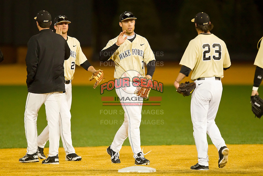 Mac Williamson #7 of the Wake Forest Demon Deacons high fives teammate Michael Dimock #23 after defeating the Georgetown Hoyas at Wake Forest Baseball Park on February 26, 2012 in Winston-Salem, North Carolina.  The Demon Deacons defeated the Hoyas 5-2.  (Brian Westerholt / Four Seam Images)