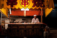 A kushiyaki stall, selling skewers of grilled beef, is lit up after dark during the festival of Onbashira.