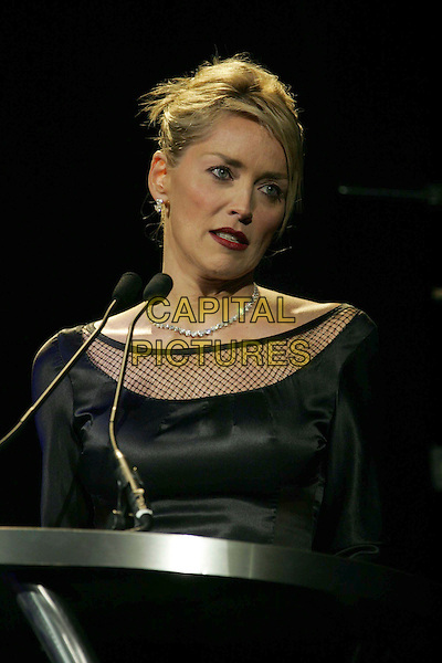 SHARON STONE.Macy's Passport 2006 - Fashion Show and Auction held at Barker Hanger, Santa Monica, California, USA,.28 September 2006..half length black fishnet dress fish net on stage microphone red lipstick.Ref: ADM/RE.www.capitalpictures.com.sales@capitalpictures.com.©Russ Elliot/AdMedia/Capital Pictures.