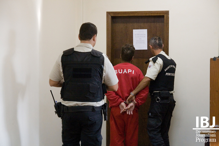 A prisoner is brought to a holding cell at Forum, a civil and criminal courthouse in Divinopolis, Brazil. Adults are accompanied by armed guards. It is illegal to use force against younger prisoners from Centro Socioeduativo and they are able to walk Forum without handcuffs. Divinopolis is where 2008 JusticeMaker Dr. Aziz Saliba is producing his educational films on habeas corpus and the Inter-American Court to teach the public about their legal rights and inform the legal profession of their options to appeal cases to courts outside of Brazil.