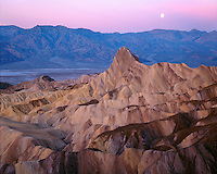 Moonset at sunset over Manly Beacon and the Panamint Range viewed from Zabriskie Point; Death Valley National Park ,CA