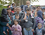 Refugees and migrants wait to walk through the Hungarian town of Hegyeshalom on their way to the border where they will cross into Austria. Hundreds of thousands of refugees and migrants flowed through Hungary in 2015, on their way from Syria, Iraq and other countries to western Europe.