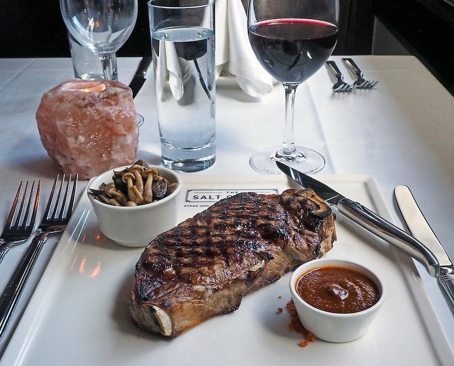 Kanasa City bone-in strip loin served with house steak sauce and mushroom conserve at The Salt Cellar. Photo by Brad Stauffer