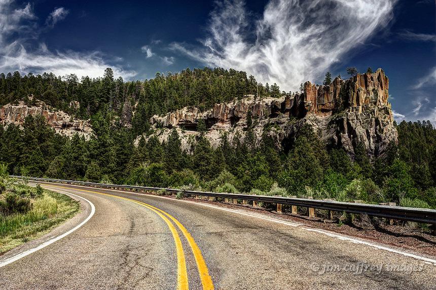 New Mexico Highway 4 as it winds through San Antonio Canyon in the Jemez Mountains north of Jemez Springs with Battleship Rock in the background