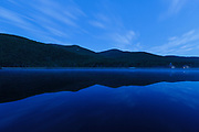 Reflection of mountain range in Saco Lake during morning blue hour in Carroll, New Hampshire during the summer months.