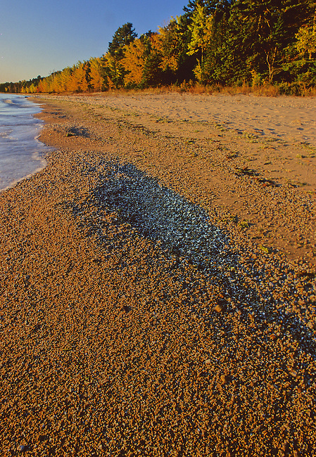 Lake Michigan waves lap the sandy shore creating sand piles on Europe Bay in Newport State Park, Door County, Wisconsin