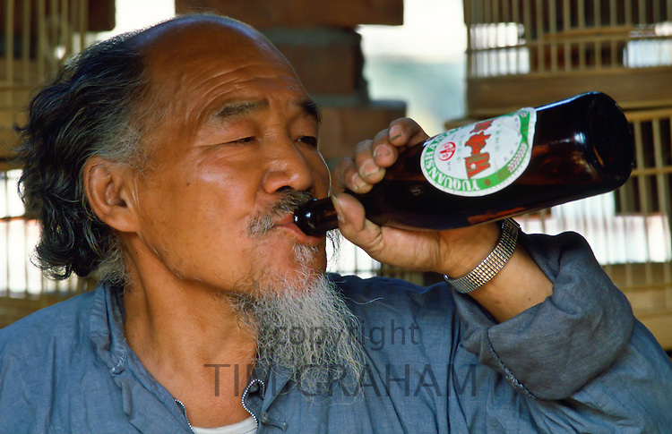 Market trader selling bird cages drinking a beer during his lunch break in Peking (Beijing) China