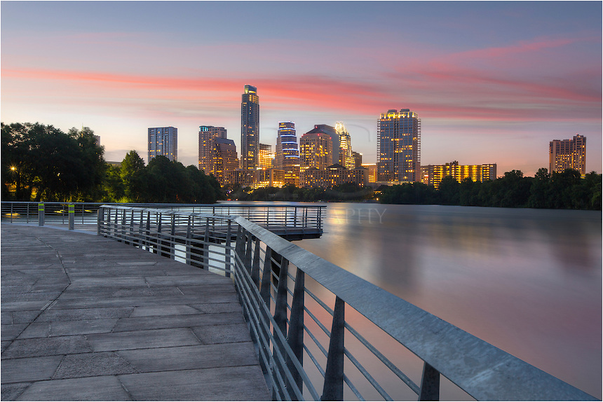 Taken in mid-June, this Austin skyline image shows the view of downtown from the newly constructed boardwalk. The highest building (currently) is the Austonian. Peaking another building is an Austin icon, the Frost Tower. This 30-second exposure created the blurred appearance of the waters flowing through Ladybird Lake.