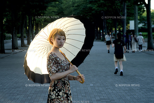 July 8, 2011 - Tokyo, Japan - A young Japanese woman holds a fashionable parasol in downtown Tokyo. Japanese people, especially middle-aged women, use parasols during the hot Summer months to avoid any form of skin cancer. Today, parasols are also becoming popular among young adult women due to various designs and colors available on the market. (Photo by Yumeto Yamazaki/AFLO)