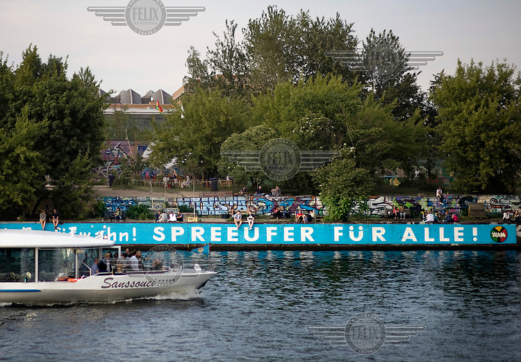 Tourist boat next to a graffiti reading Kiez statt Profitwahn Spreeufer Fuer Alle at the Bar Yaam, protest against the Mediaspree city project with building site Caimmo of the company CA Immo by the river Spree in Berlin Kreuzberg-Friedrichshain.