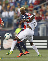 New England Revolution forward Dimitry Imbongo (92) attempts to control the ball as Toronto FC defender Doneil Henry (4) closely defends. In a Major League Soccer (MLS) match, Toronto FC (white/red) defeated the New England Revolution (blue), 1-0, at Gillette Stadium on August 4, 2013.
