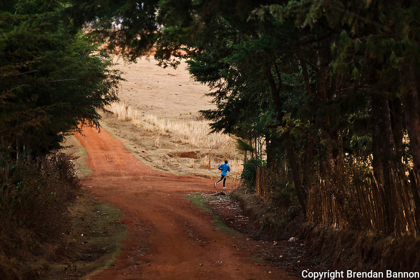 A lone runner on the dirt roads of Iten, Kenya. Iten is home to some of the world's fastest marathon runners and has been at the center of a revolution in marathon race times in recent years. The athletes benefit from high altitude training as well as regimines that have introduced speed into training as a primary concern.