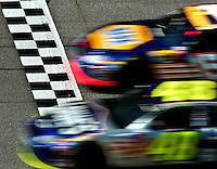 The cars of NACSAR Nextel Cup Series drivers #15 Michael Waltrip and #48 Jimmie Johnson are a blur as they cross the finish line at Daytona International Speedway during the second of two 125 mile qualifying races.