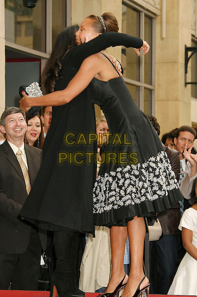 SALMA HAYEK & VANESSA L. WILLIAMS.Vanessa L. Williams Celebrates Her Birthday With a Star On The Hollywood Walk of Fame, Holllywood, California, USA..March 19th, 2007 .full length black dress floral print heels clear clutch purse coat hug embrace.CAP/ADM/RE.©Russ Elliot/AdMedia/Capital Pictures