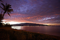The view from Maalaea, Maui.  Kihei and Wailea lights line the shore in the distance while a colorful sunrise blankets Mount Haleakala.