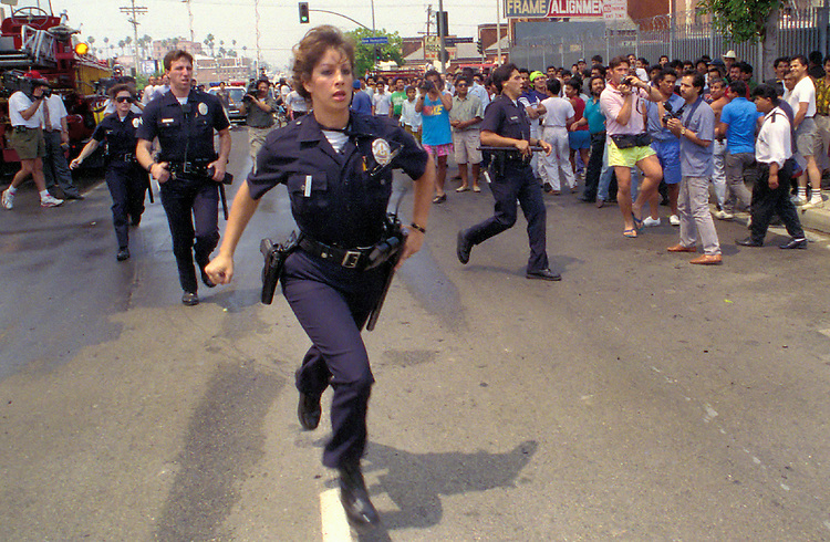 "A olice woman runs into the fray of looting during the ""uprising"" of rioting and looting in the Koreatown neighborhood of Los Angeles, Calif. following the acquittal of LAPD officers accused of beating motorist Rodney King, May 30, 1992. Photo copyright Gerard Burkhart 818-207-0273)during the ""uprising"" of rioting and looting in the Koreatown neighborhood of Los Angeles, Calif. following the acquittal of LAPD officers accused of beating motorist Rodney King, May 30, 1992. Los Angeles suffered city wide chaos and destruction following the the end of the first trial against accused officers Sergeant Stacey Koon, Laurance Powell, Theodore Briseno and Timothy Wind. A later  Federal Civil Rights Trial sent officers Powell and Koon to prison for 30 months while Briseno and Wind were acquitted. Photo copyright Gerard Burkhart 818-207-0273)"
