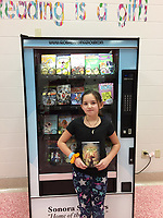 NWA Democrat-Gazette/DAVE PEROZEK Sophie Lawson, 9, a fourth-grader at Springdale's Sonora Elementary School, poses Tuesday, Feb. 4, in front of the school's new book vending machine with a book she got from it for being chosen the kindest student in her class by her classmates.
