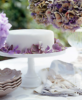 This iced cake is simply decorated with purple Hydrangea petals