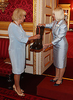 12 July 2016 - London, England - CCamilla, Duchess of Cornwall, is presented with some customised, Orange laces for lace up for bones, Dubarry Boots as she hosts the 30th Anniversary Garden Party for the National Osteoporosis Society in St James Palace in London. Due to inclement weather the event was moved indoors. The Duchess of Cornwall has been connected with the charity for nearly 30 years. Photo Credit: ALPR/AdMedia