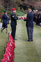 A Canadian soldier hands a poppy wreath to a United States veteran at a Remembrance Day ceremony at the Yokohama War Cemetery, Hodogaya. Yokohama, Japan. Sunday November 9th 2014