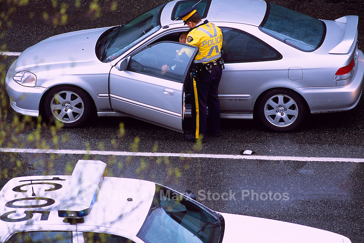 RCMP Police Officer writing Ticket for Traffic Violation Incident to Motorist in Car, Vancouver, BC, British Columbia, Canada