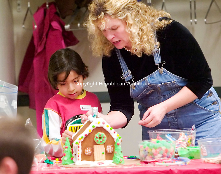 SOUTHBURY, CT- 05 DEC 2007- 120507JT17-<br /> Nancy Stuart-Ploch shows Arturo Ortega, 8, how to make a gingerbread house at the Southbury Public Library during a children's program taught by Stuart-Ploch, a teacher at the Silo in New Milford on Wednesday.<br /> Josalee Thrift / Republican-American