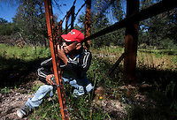 A Mexican man untangles himself from barbed wire while crossing the border fence illegally from Mexico into Arizona in the desert outside Nogales. (Pat Shannahan/ The Arizona Republic)
