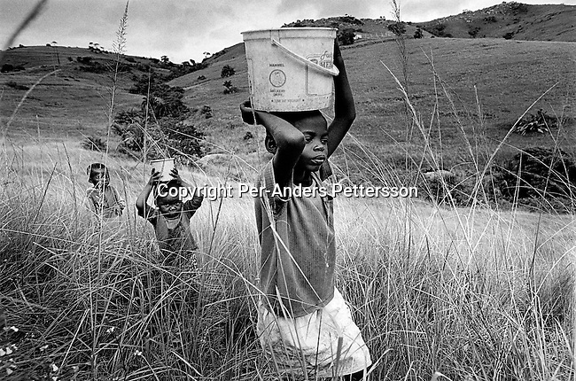 Bongekile Ntuli, age 11, carries a bucket of water on her head together with her two younger siblings on January 31, 2002 in their small house in Port Shepstone, in Natal Province, South Africa. Bongekile is a victim of sexual abuse and has been repeatedly abused by her father and his brothers for years. Bongekile's mother died of an Aids related disease in 2001 and now she lives with her aunt and grandmother. South Africa is struggling with one of the highest rates of rape of in the world. (Photo by: Per-Anders Pettersson)