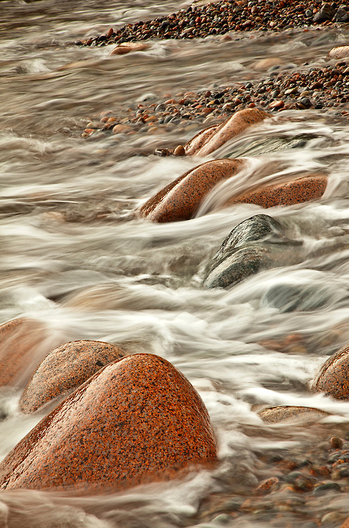 Ocean waves dance among the granite cobblestones on Hunters Beach in Acadia National Park, Maine, USA