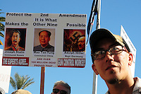 "Phoenix, Arizona. January 19, 2013 - A man listens as several speakers address the crowd during Saturday's rally on Phoenix. In the background, a sign in favor of protecting the Second Amendment includes photos of Joseph Stalin, Mao T'se-tung and Adolf Hitler. As President Barack Obama proposed new gun regulations last week, gun owners demonstrated against it with national ""Guns Across America"" rallies to defend the Second Amendment. Dozens showed up at the Arizona State Capitol, many of them carrying weapons. Photo by Eduardo Barraza © 2013"