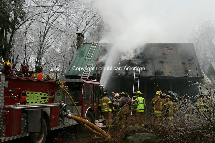 WINSTED, CT - 12 December, 2008 - 121208MO02 - Firefighters from Winsted and Winchester Center douse the last of the flames at 113 Highview Drive Friday morning. A fire that started in or near a generator caused heavy damage to the home, but no injuries resulted. Jim Moore Republican-American.